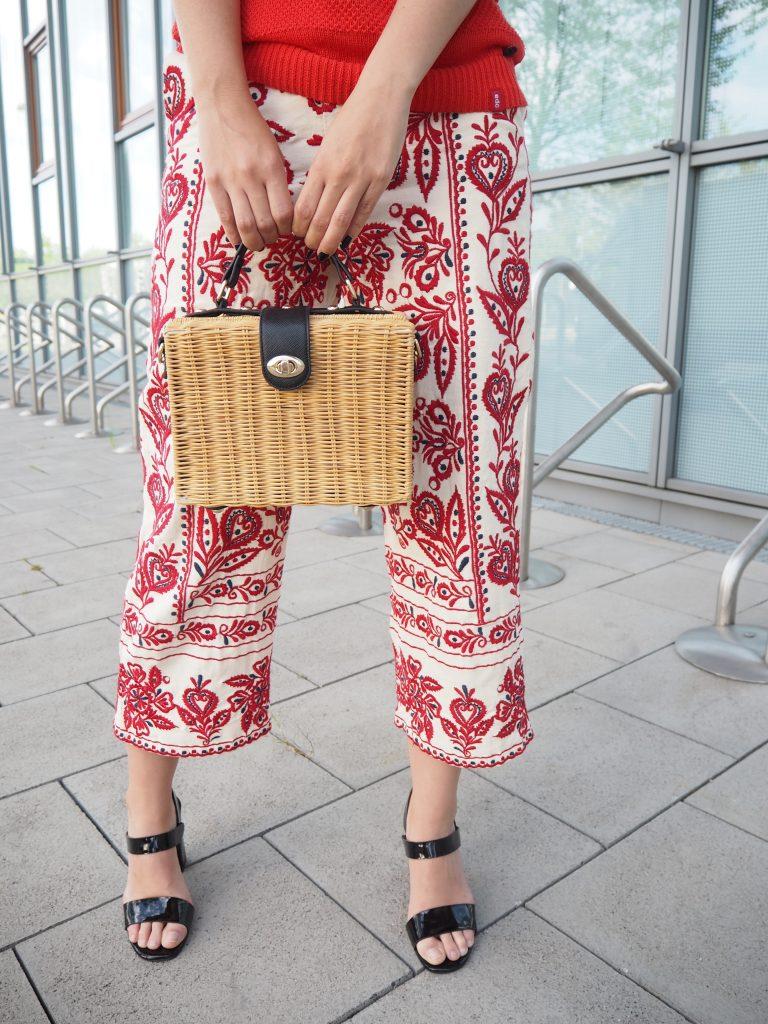 Korbtasche und Sandaletten als Accessoires zu bestickter Culotte
