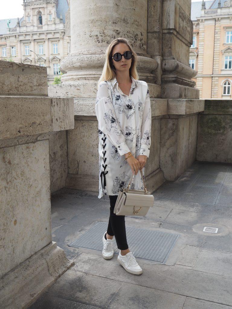 Oversize Bluse mit floralem Print schwarze Lederhose und weiße Sneaker